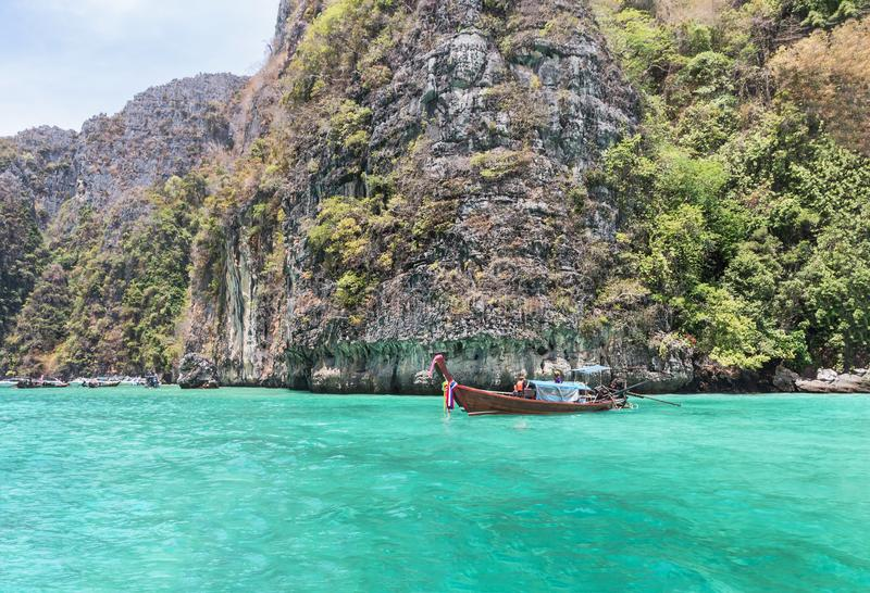 Longtail boat moored floating at Pileh bay is blue lagoon with limestone rock at phi phi island Krabi,Thailand. royalty free stock images