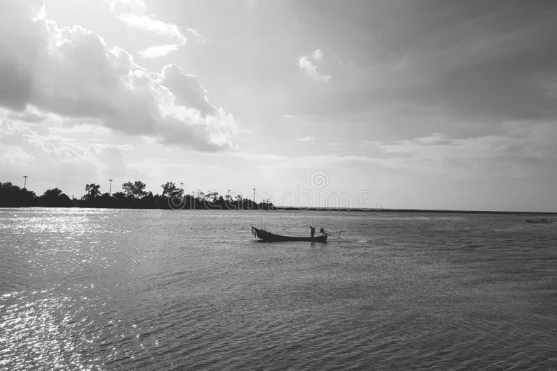 Longtail boat on water at bay. Sea, seashore, river, longtail-boat, traveling, tourism, trip, journey, transport, transportation, coast, ocean, black, white stock images