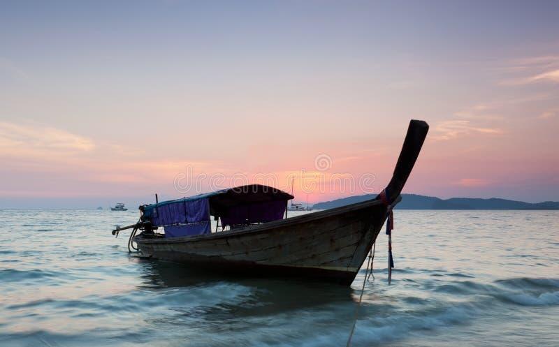 Longtail contra una puesta del sol. imagen de archivo libre de regalías