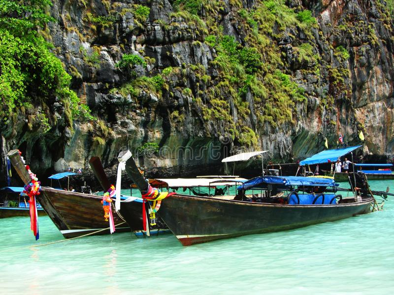 Longtale boats at the Phuket beach with limestone rock on background in Thailand. Phuket island is a most popular tourist destinat royalty free stock photography