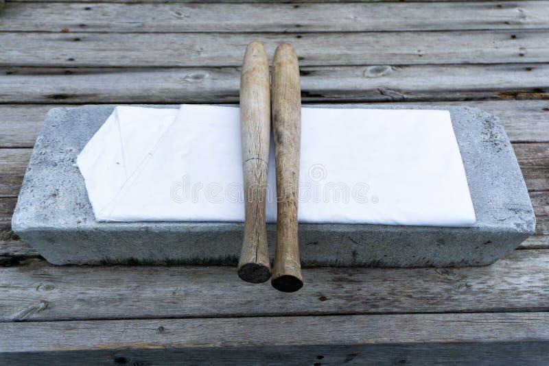 """Longtemps, utilisation ronde de batte en bois pour les tissus battus appelés le """"pangmangi """"et utilisation à plat en pierre pour  photo stock"""
