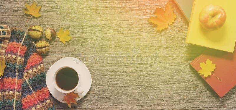 Longue bannière des feuilles rouges, vertes et jaunes d'automne, des pommes avec la tasse de café ou du thé avec des livres sur l image stock