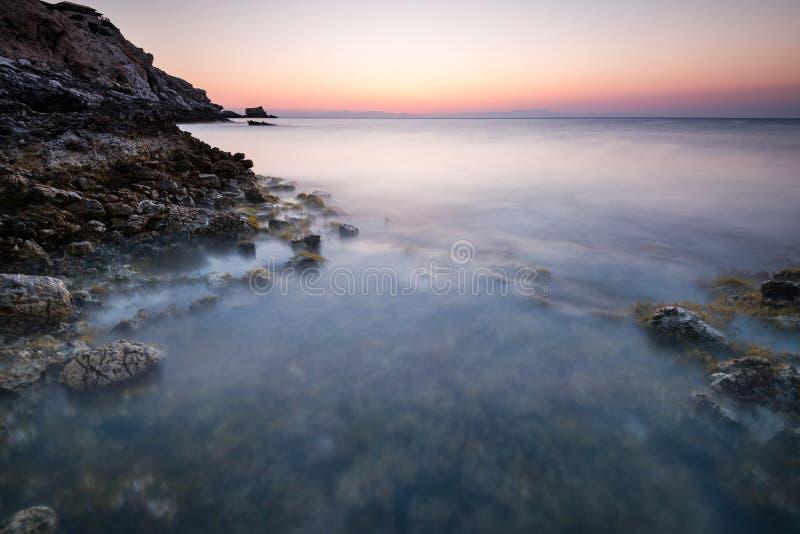 Longue exposition au lever du soleil sur les falaises rocheuses en mer, Grèce images stock