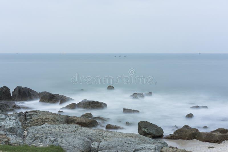 Longue exposition de vague et de roche de mer au lever de soleil photo stock