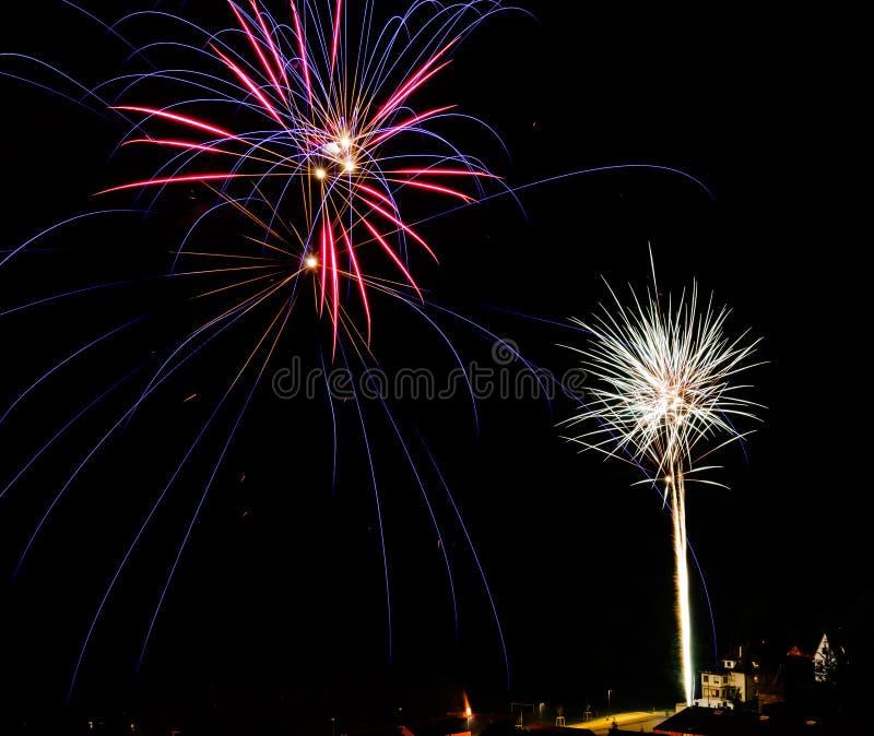 Longue exposition des feux d'artifice multicolores contre un ciel noir photos libres de droits
