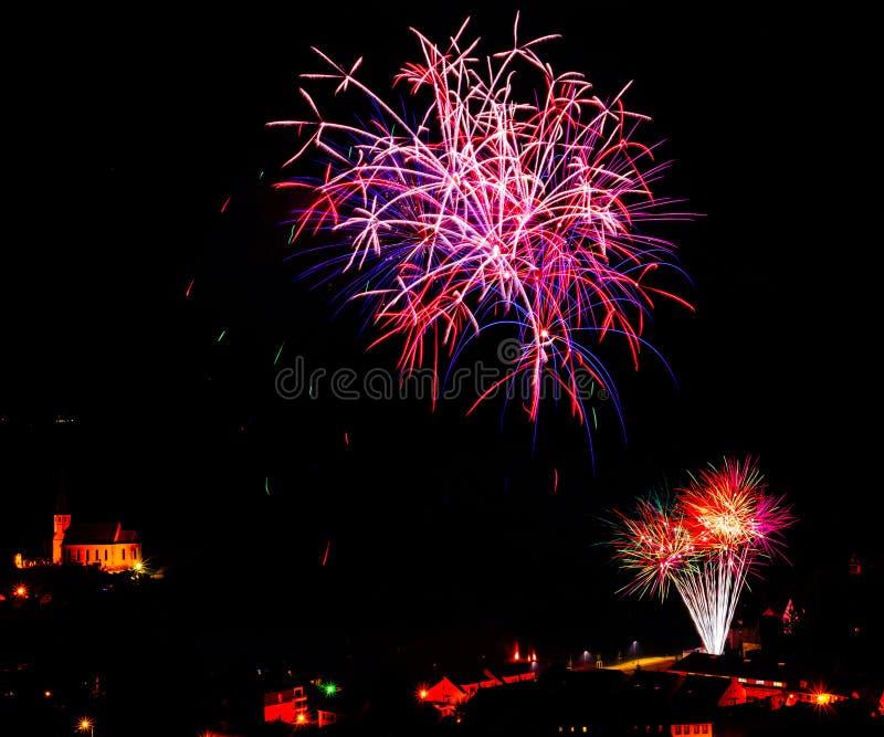 Longue exposition des feux d'artifice multicolores contre un ciel noir photos stock
