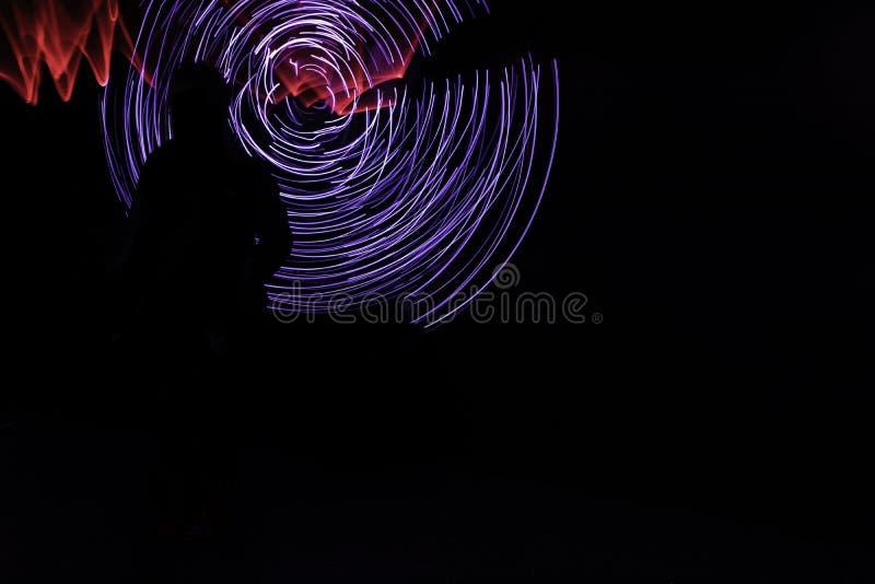 Longue exposition des lumières circulaires bleues avec la brume rouge derrière la silhouette images libres de droits