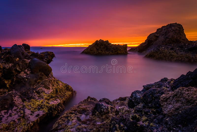 Longue exposition des vagues et des roches dans l'océan pacifique au coucher du soleil image libre de droits