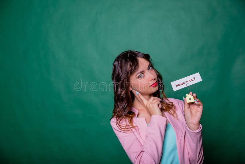 Longue fille de cheveux bouclés faisant face à un choix sur le vert, tenant la petite maison à ses mains avec le message, la ques photographie stock libre de droits