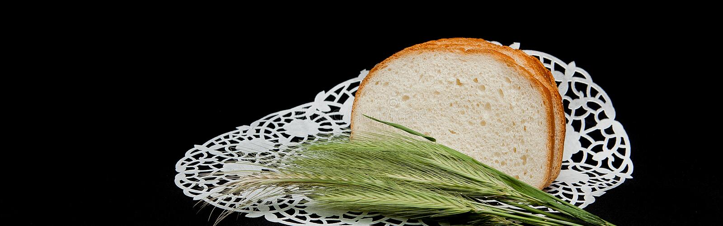 Longue miche de pain coupée en tranches, décorée des transitoires de blé sur le fond noir Transitoire de blé sur un fond noir Con photo libre de droits