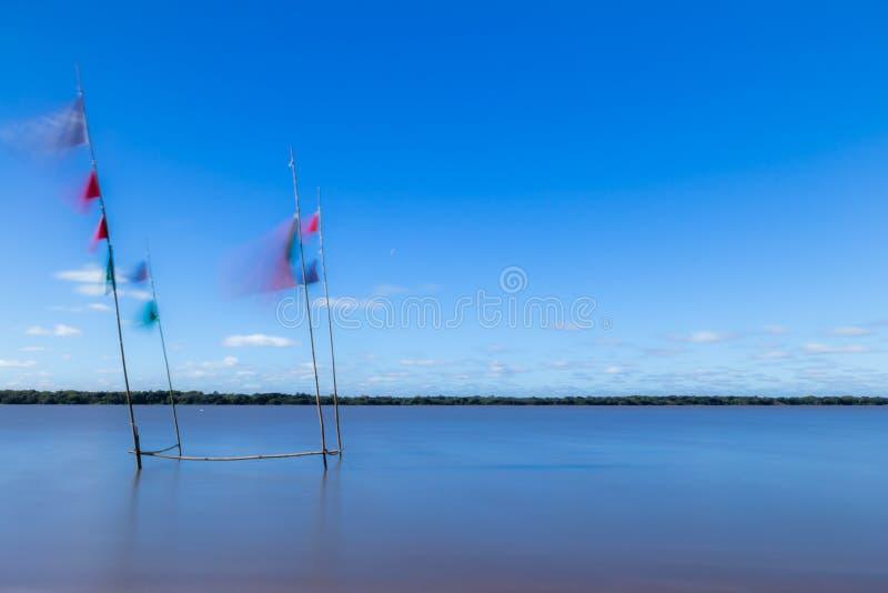 Longue photographie d'exposition Petite plage au bord de la rivi?re Le vent d?place les drapeaux photo stock