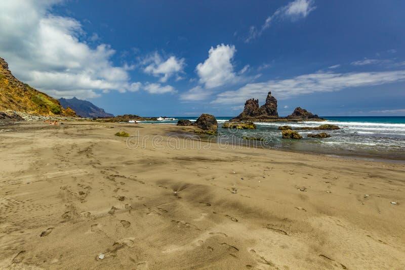 Longue plage naturelle Benijo avec des empreintes de pas dans le sable Roche de lave dans l'eau Horizon de mer bleu, fond naturel image libre de droits