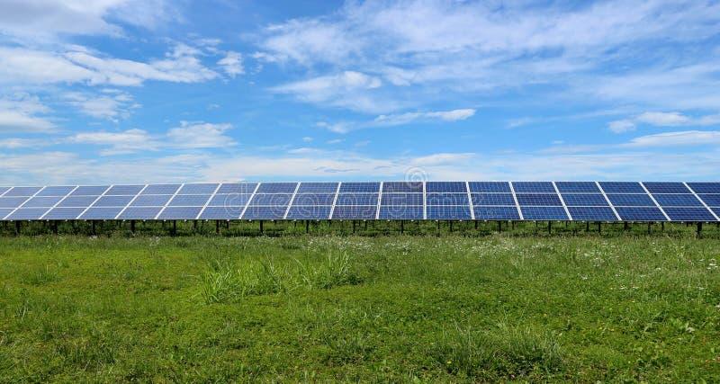 Longue rangée des panneaux solaires dans un pré, entre l'herbe verte et les nuages se déplaçant le ciel image stock