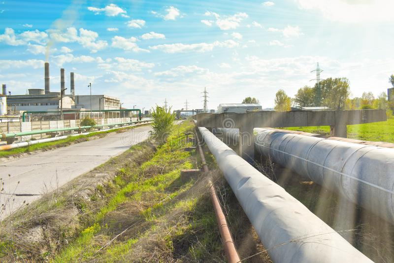 Longue route dans la zone industrielle près de l'usine chimique La nature essaye de résister là images stock
