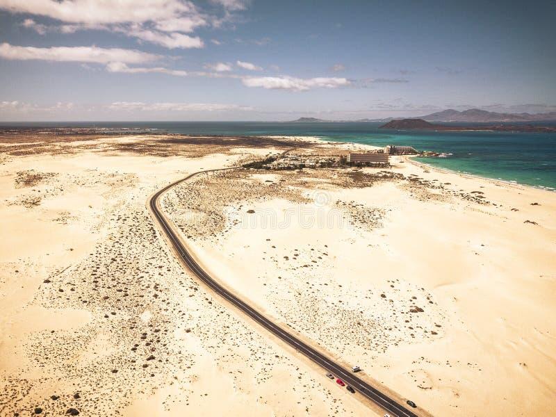 Longue route goudronnée avec désert et plage de sable de part et d'autre - vue aérienne haute avec océan et îles sur fond - image libre de droits
