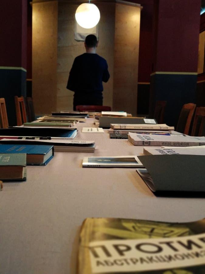 Longue table avec des livres et un homme reculant à l'arrière-plan images libres de droits