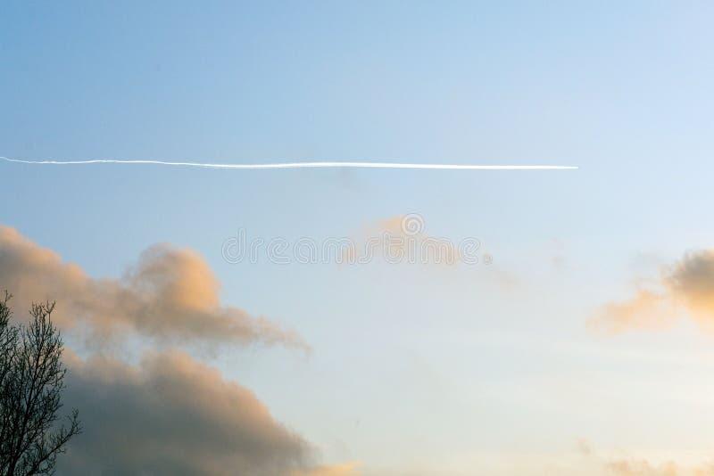 Longue traînée blanche d'un avion à réaction dans le ciel bleu au temps de coucher du soleil photo stock