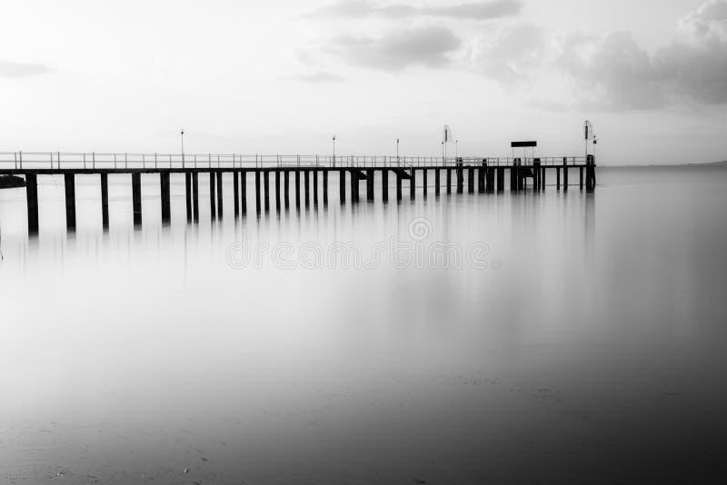 Longue vue d'exposition d'un pilier sur un lac au coucher du soleil, avec beau images stock