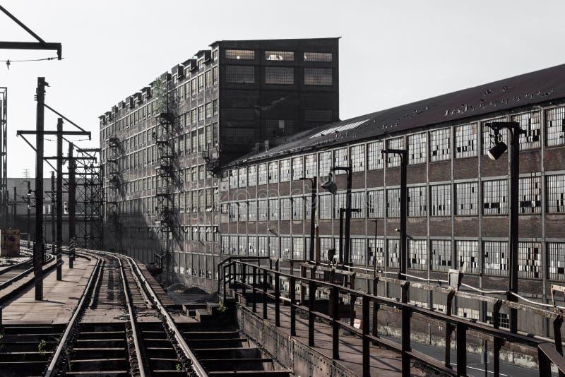 Longue vue des voies de train à côté des entrepôts expansifs de la brique avec des murs des fenêtres, complexe industriel image stock