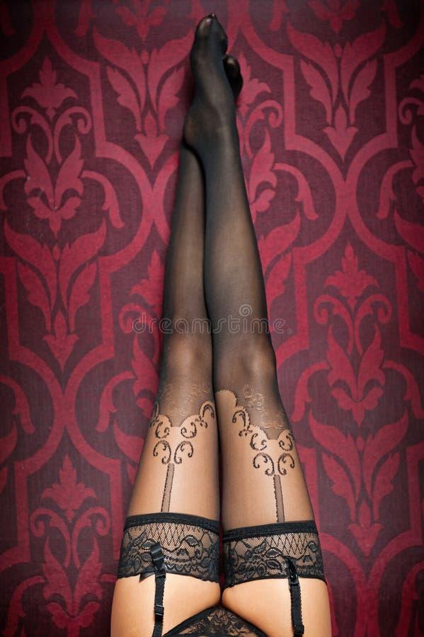 Longues jambes dans les bas et des culottes noirs image libre de droits