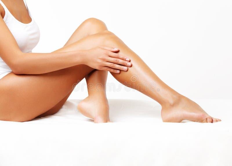 Longues jambes de femme d'isolement sur le blanc. Dépilage image libre de droits