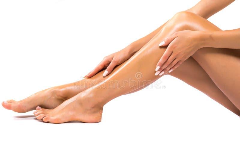 Longues jambes de femme d'isolement sur le blanc Dépilage Cosmétiques, soins de santé photos stock
