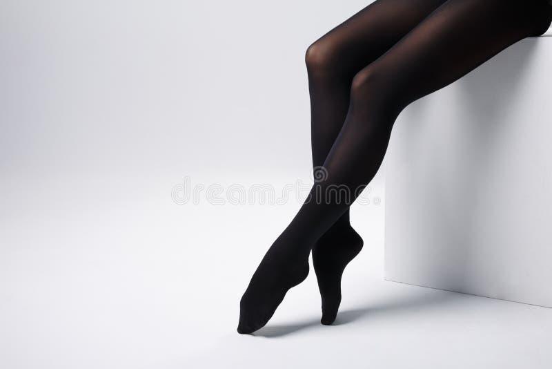 Longues jambes femelles sexy minces dans le collant noir sur la boîte de studio photos stock