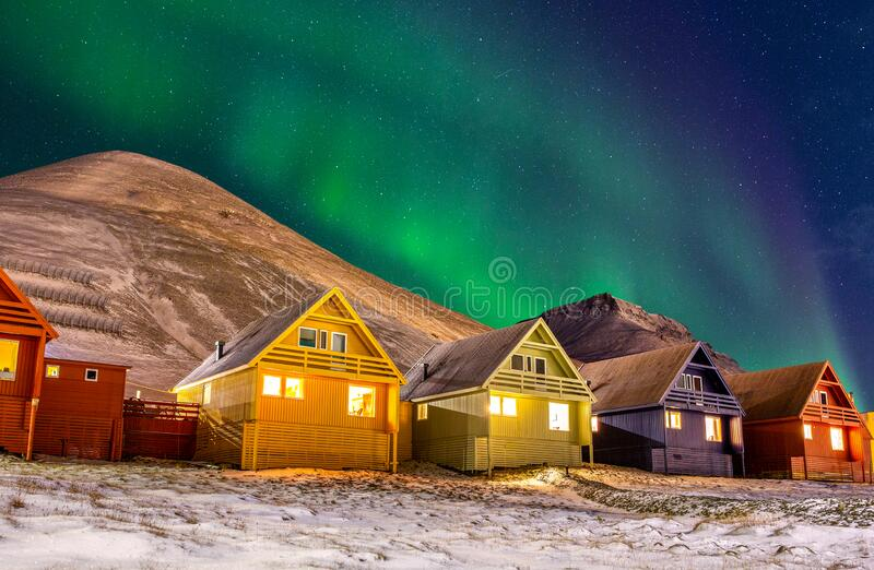 Longyearbyen colorful houses with Aurora Borealis in the sky full of stars. Photograph taken in November 2019 during the polar night in the northenmost town in