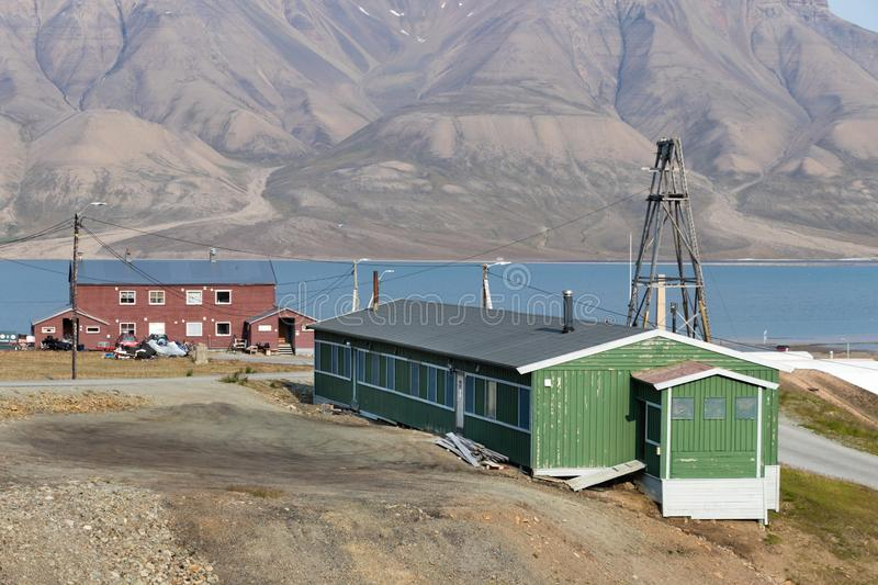 Colorful wooden houses along the river in summer at Longyearbyen, Svalbard. Longyearbyen, Svalbard, Norway - August 13th, 2018: Colorful wooden houses along the royalty free stock image