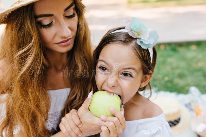 Lonkg-haired curly young woman with trendy makeup feeding daughter with green apple. Brunette little girl eating juicy. Lonkg-haired curly young women with royalty free stock photos