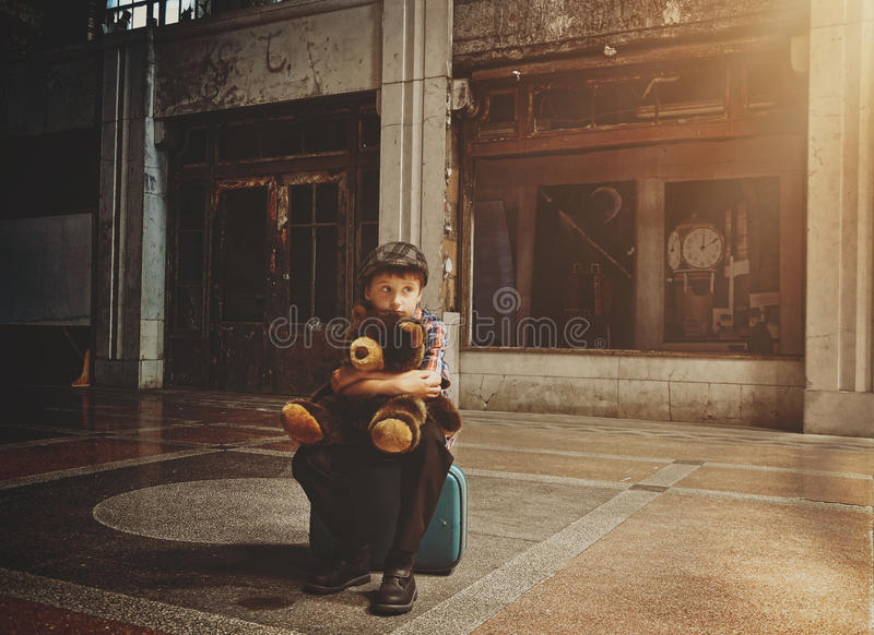 Lonley Boy Waiting for Safety in Old Building. A scared young boy is sitting on a travel suitcase in an old building holding a teddy bear for a loneliness or stock photos