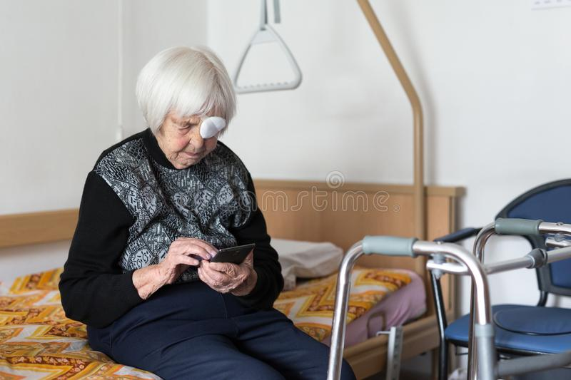 Lonley elderly 95 years old woman sitting at the bad using modern mobile phone. royalty free stock images