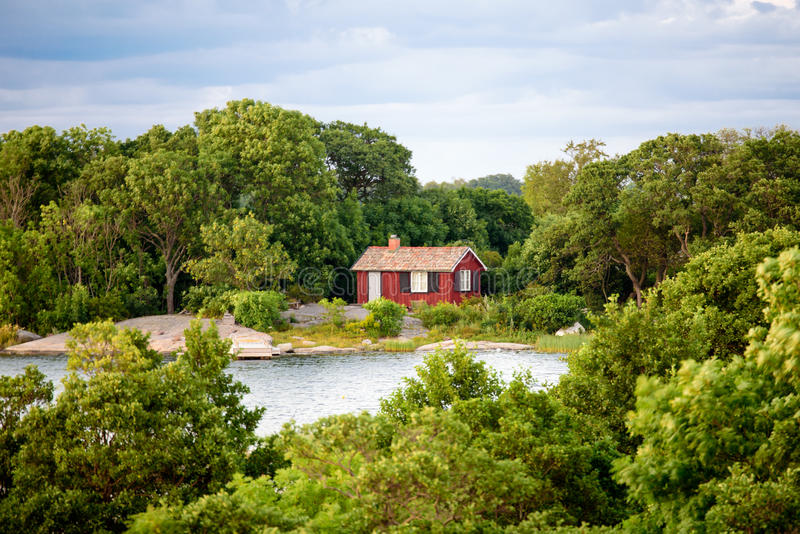 Lonley red hut. A lonley old red hut on an island in the archipelago. Embedded by green trees. Small bay in front of the house. Cloudy sky. Stockholm, Sweden stock image