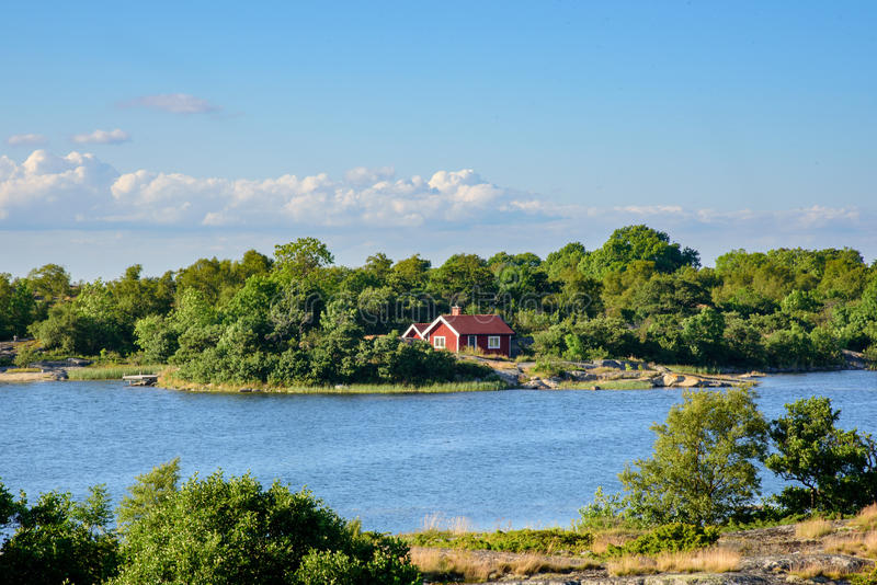Lonley red hut. A lonley old red hut on an island in the archipelago. Embedded by green trees. Water in front f the house. Blue sky. Stockholm, Sweden stock images