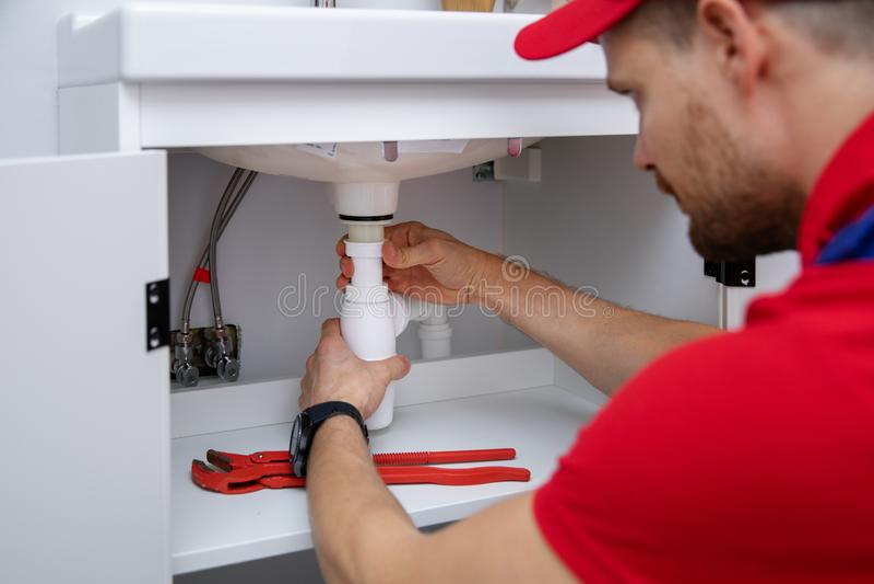 Loodgieter die in badkamers werken die gootsteensifon installeren stock afbeelding