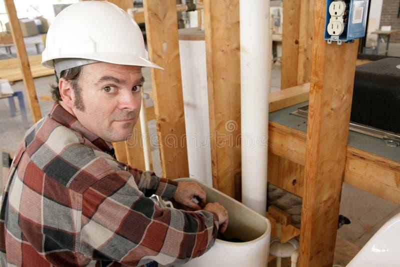Loodgieter die in de Tank van het Toilet werkt stock afbeelding