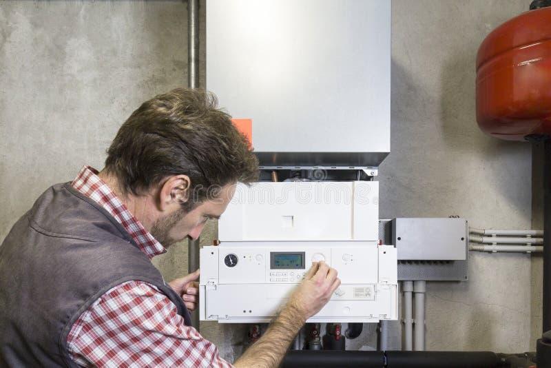 Loodgieter die een condenserende boiler herstellen royalty-vrije stock fotografie