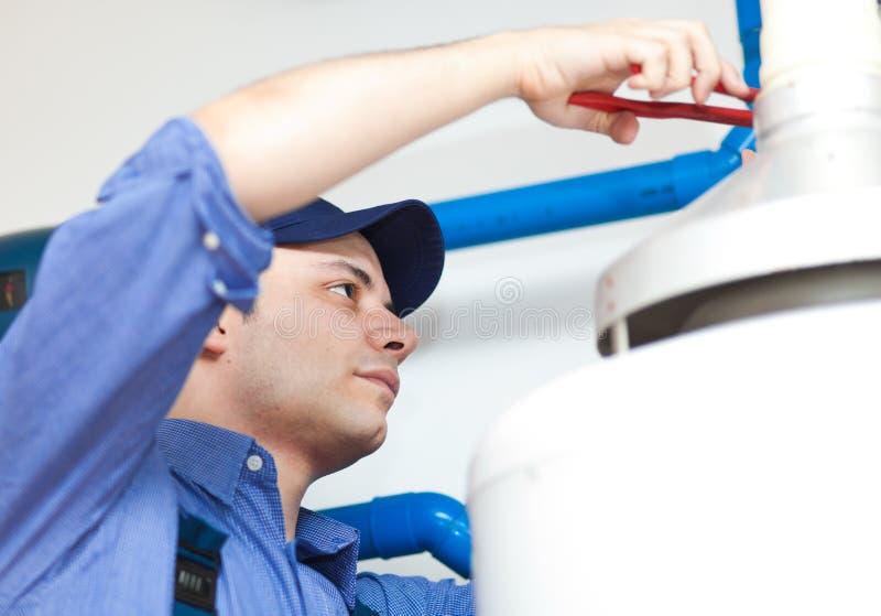 Loodgieter die een warm waterverwarmer herstellen royalty-vrije stock afbeelding