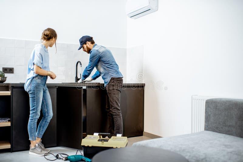 Loodgieter die keukentapkraan met vrouw in de flat herstellen stock foto's
