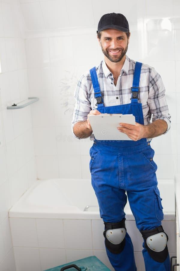 Loodgieter die nota's over klembord nemen royalty-vrije stock foto