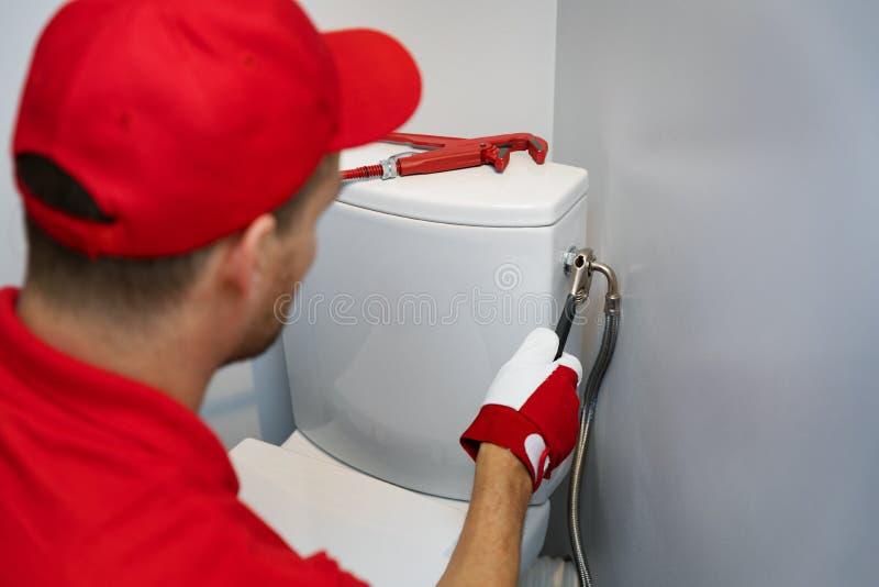 Loodgieter die in toilet werken die flexibele waterpijp installeren aan WC-tank stock foto