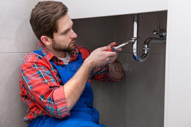 Loodgieter het werken stock afbeeldingen