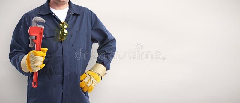 Loodgieterhand met moersleutel stock afbeelding