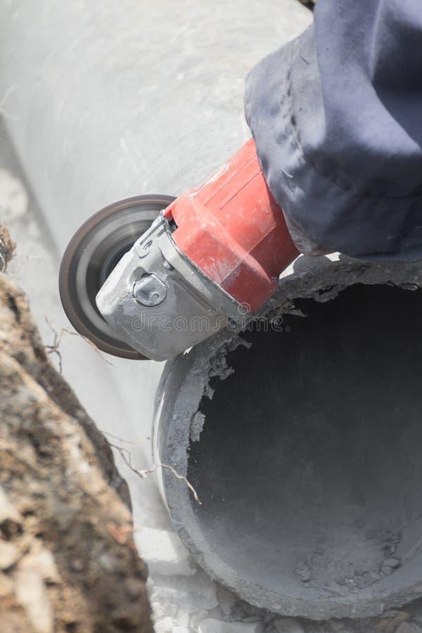 Loodgieters die concrete waterpijpen snijden stock fotografie