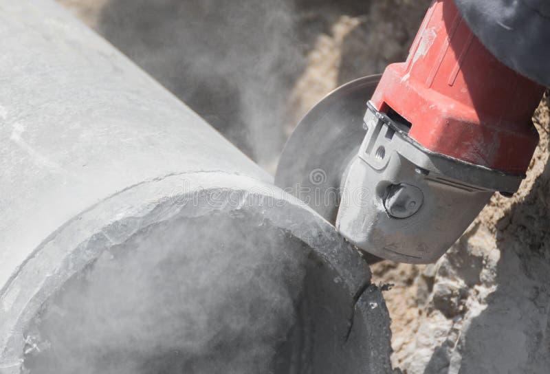 Loodgieters die concrete waterpijpen snijden stock afbeelding