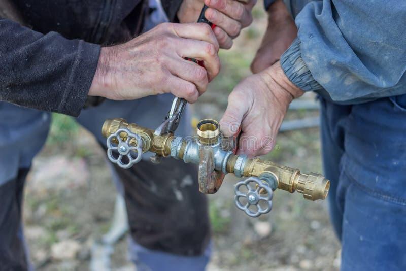 Loodgieters die gebruikend pijpmoersleutels 3 werken stock foto