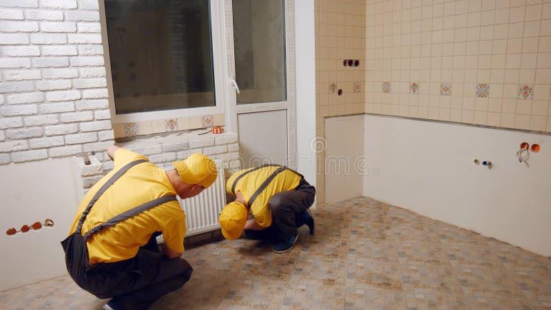 Loodgieters die het verwarmen radiator installeren stock fotografie