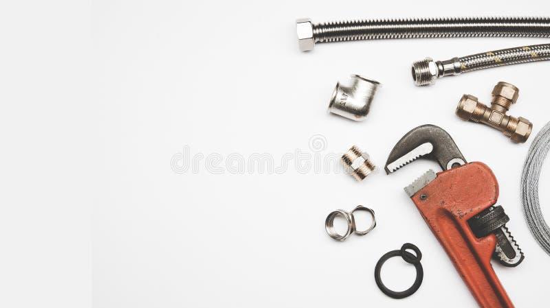 Loodgieterswerkhulpmiddelen en materiaal op witte achtergrond met exemplaarruimte stock foto's