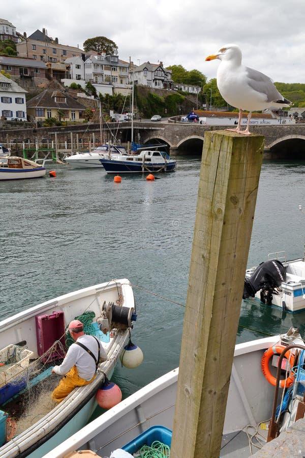 """LOOE, CORNWALL, BRITISCHES †""""am 17. Mai 2015: Fischereihafen Looe mit einem Fischer, der an seinem Fischernetz arbeitet stockfotos"""