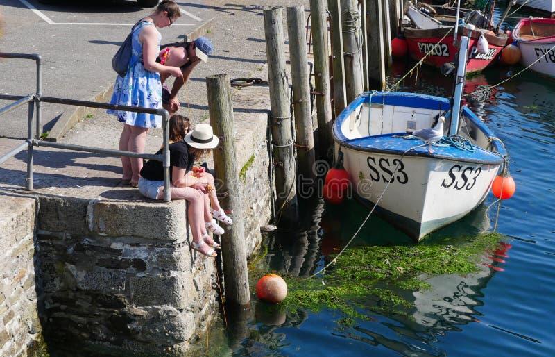 Looe, Cornwall, het UK, 14 Juli, 2019 Zonnige hete Zondag in Cornwall met kinderen en volwassenen die krab gebruiken royalty-vrije stock foto